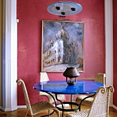 Round table with blue-lacquered top and rattan chairs in traditional living room with walls painted dusky pink