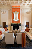 Grand salon with coffered ceiling and pale, classic upholstered seating in front of open fireplace