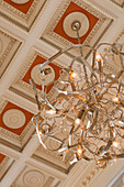 Modern chandelier hanging from coffered ceiling