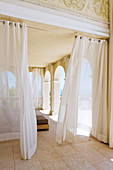 Veranda of grand villa with airy curtains hanging in front of arcade