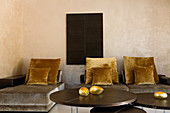 Sofa and couch with grey velvet upholstery and gold cushions in minimalist room
