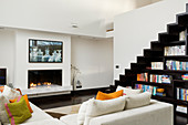 Corner sofa in front of gas fireplace in two-storey living room with zigzag staircase above custom-made bookcase