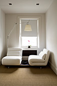 Small, elegant guest room with folding armchair elements and designer lamp by Artemide