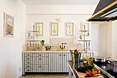 Retro country house style in French kitchen-dining room with brass shell handles on light grey striped cupboard doors