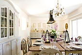 Festively set table in large kitchen-dining room with vintage French-style dining area and dresser