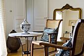 Holzstühle mit Korbgeflecht und alter Bistrotisch mit Porzellan-Urne als kleine Sitzgruppe in renoviertem Landhaus