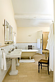 Ensuite bathroom in French country house style with retro pedestal sinks and free-standing bathtub
