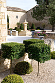 Stone fountain in courtyard of grand country house; topiary box cubes in foreground