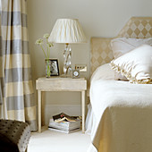 Table lamp with white fabric shade on pale side table next to bed with upholstered headboard on wall
