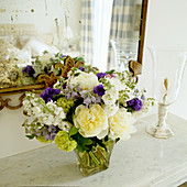 Bouquet on marble shelf in front of mirror with dull spots