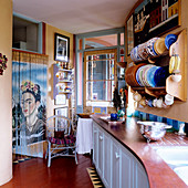 Kitchen counter below plates in wall-mounted plate rack opposite thread curtain with portrait of Frida Kahlo in doorway