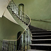 Vintage stairwell - spiral staircase with wrought iron balustrade and niches in gray-green painted walls