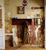 Coat hanging on wooden coat rack on wall with peeling paint in simple hallway