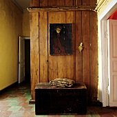 Old chest below painting on wooden wall in simple hallway