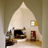 View of open fireplace in simple room through Oriental pointed archway