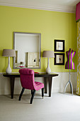 Art Deco-style living room - chair with pink upholstery in front of elegant table lamps on console table against yellow-painted wall