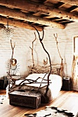 Bed hand crafted from twisted branches in rustic bedroom with wood-beamed ceiling
