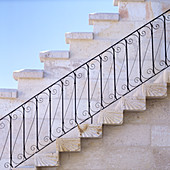 Staircase with wrought iron balustrade running along outside house wall