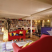 Red sofas and full bookcase in festively decorated loft apartment with corrugated sheet metal ceiling