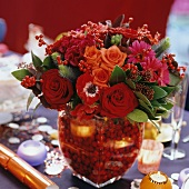 Bouquet in various shades of red in matching glass vase with red decorative beads