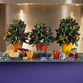 Small Christmas tree arrangements with brightly wrapped sweeties and colourful fir cones