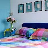 Cheerful colour scheme in bedroom with checked bed linen below pictures on turquoise mounts combined with light blue sliding door