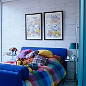 Wrapped presents on checked bed linen and colourful still-life paintings on white, concrete block wall