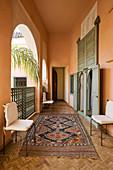 Orientteppich auf Parkett mit Fischgrätmuster in Loggia eines marokkanischen Wohnhauses