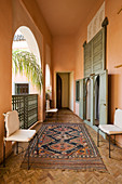 Oriental rug on herringbone parquet floor of loggia of Moroccan house