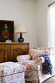 Armchair and matching footstool with patterned upholstery in front of half-height cabinet in corner of room