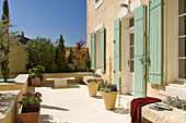 Sunny terrace with plant pots in front of a Mediterranean home
