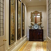 Decorative plate on antique, half-height cabinet below gilt-framed mirror in manorial hallway