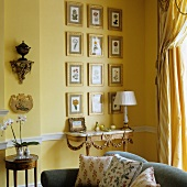View across modern sofa to antique console table against yellow-painted wall and gilt-framed pictures with floral motifs