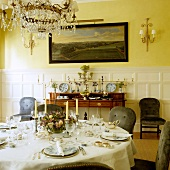 Festively set dinner table in grand dining room with yellow-painted walls and half-height, white wood panelling