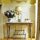 Plant pot and table lamp on antique console table with gilt carved ornamentation against white wood panelling