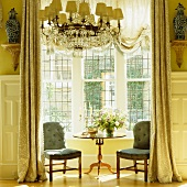 Refined seating area in bay window with floor-length curtains in grandiose interior
