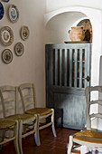 Kitchen chairs against wall below decorative wall plates and rustic wooden door of fitted cupboard in corner of Mediterranean dining room