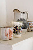 Vintage china beakers and jug with traditional motifs on shelf