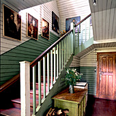 Oils portraits exhibited in simple stairwell of Nordic wooden house
