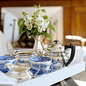 Vase of flowers on tray with teacups and silver teapot