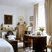 Schlafzimmer mit antikem Schreibtisch vor Fenster mit bodenlangem, drapierten Vorhang