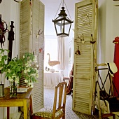 Vintage-style room with open folding doors and view of lantern-shaped pendant lamp and table in background