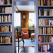 Open doorway in bookcase showing view of country-style armchair