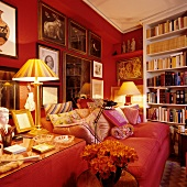 Corner of traditional living room with red sofa against red wall with framed pictures