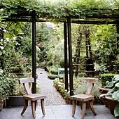 Rustikal moderne Holzstühle auf Terrasse unter berankter Pergola und Blick in blühenden Garten