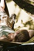 Mädchen liegt auf Liegestuhl im Garten