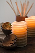 Wooden spoon and lit candles in front of bowl of joss sticks