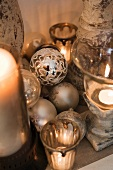 Silver Christmas baubles next to candle holders with lit candles