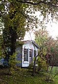 Autumnal atmosphere in garden with small wooden hut