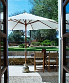 View of seating area on terrace with parasol and garden through open door